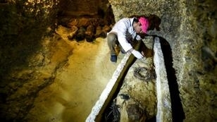 An archaeologist brushes a newly-discovered mummy laid inside a sarcophagus found in burial chambers dating to the Ptolemaic era (323-30 BC) at the necropolis of Tuna el-Gebel in Egypt's southern Minya province, on February 2, 2019