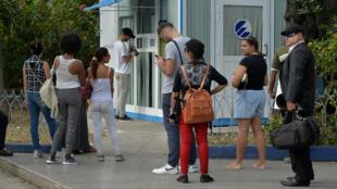 Des Cubains utilisent leur téléphone pour se connecter à Internet via le wifi dans un parc à La Havane, le 5 décembre 2018.