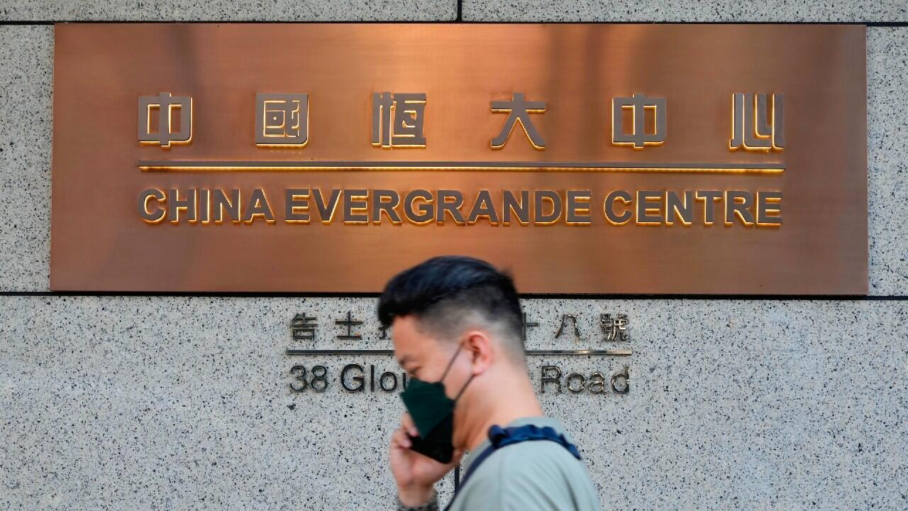 A man walks past the entrance to the China Evergrande Group headquarters in Hong Kong on Monday, Oct. 4, 2021.