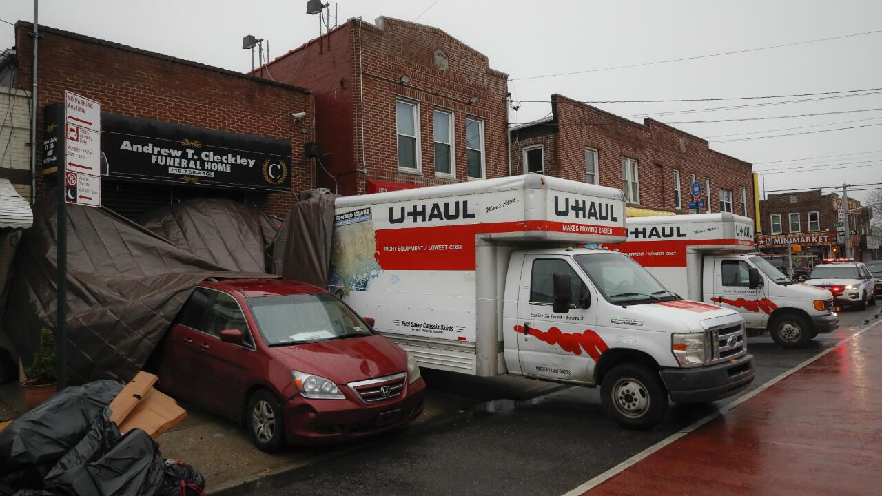 Un vehículo de la policía de Nueva York está estacionado junto a dos camiones de mudanzas fuera de la funeraria Andrew T. Cleckley, el jueves 30 de abril de 2020, en el distrito de Brooklyn de Nueva York.