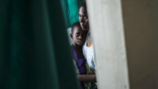 Une mère séropostive tient son enfant malade sans ses bras, au Malawi, en novembre 2014.