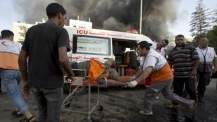 Des ambulanciers s'occupent d'une victime d'un raid aérien israélien à Gaza, le 30 juillet 2014.