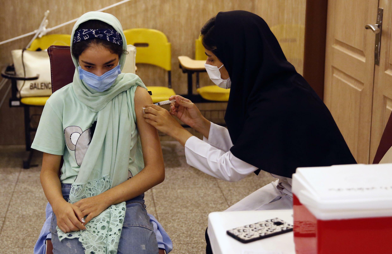 Una colegiala recibe una vacuna Covid-19 en una escuela en Teherán, 7 de octubre de 2021
