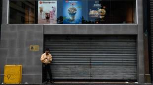 Un hombre come un postre al lado de un restaurante de McDonald's cerrado en Caracas. 2/9/18