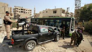 Des forces pro-gouvernementales syriennes surveillent l'évacuation d'un bus de la ville de Daraya après un accord entre le régime et l'opposition suite à quatre années de siège.