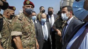 El presidente libanés Michel Aoun (centro) visita el 5 de agosto de 2020 el lugar donde se produjeron las explosiones