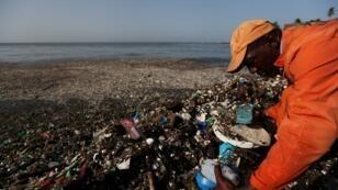 Un trabajador remueve plástico y otros escombros durante una limpieza en las orillas de la playa de Montesinos, en Santo Domingo, República Dominicana, el 19 de julio de 2018.