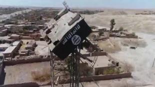 """راية تنظيم """"الدولة الإسلامية"""" تتهاوى من على برج مياه في قرية أبو ماريا بتلعفر"""