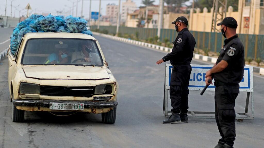 Agentes de la policía palestina controlan la llegada de un vehículo a una zona cortada por la imposición de cuarentenas estrictas. En Gaza, el 4 de septiembre de 2020.