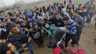Des manifestants palestiniens transportent un homme blessé suite aux clashes avec la police israélienne, le 15 décembre, 2017 dans la bande de Gaza.
