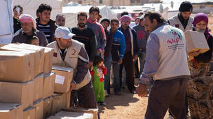 Des volontaires d'une ONG libanaise distribuent des vivres aux réfugiés syriens du camp de Arsal à l'est du Liban, le 25 octobre 2014.