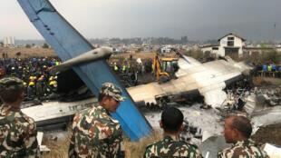 Los restos de un avión de la compañía US-Bangla que se estrelló mientras aterrizaba en el aeropuerto internacional Tribhuvan. Los trabajadores de rescate miran el siniestro ocurrido en el aeropuerto de Katmandú, Nepal, el 12 de marzo de 2018.