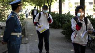 طلاب يضعون الكمامات عند وصولهم الى المدرسة في بكين في 11 ايار/مايو 2020.