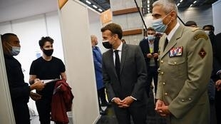 French President Emmanuel Macron (C) and Commander of the Paris fire department, the Brigade de sapeurs-pompiers de Paris (BSPP), General Jean-Marie Gontier (R) speaks with a member of the public as they visit a giant Covid-19 vaccination centre during its inauguration at the Porte de Versailles convention centre in Paris on May 6, 2021.
