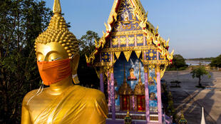 A face mask was placed on the face of a giant Buddha statue outside Bangkok