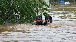 Un hombre rescata a otro de morir ahogado debido a los desbordamientos de varios ríos por las lluvias monzónicas en Cochín, India, el 16 de Agosto de 2018.