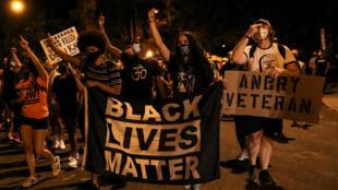 La gente marcha con carteles, en protesta contra la violencia policial y por la igualdad racial en Washington, EE. UU., el 5 de septiembre de 2020.