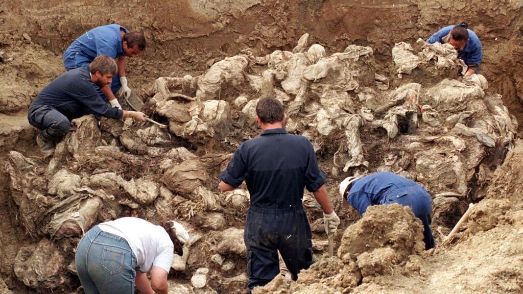 Varios forenses examinan docenas de cuerpos enterrados en una fosa común por las tropas serbobosnias. Imagen tomada el 18 de septiembre de 1996 cerca de Srebrenica, en Bosnia y Herzegovina.
