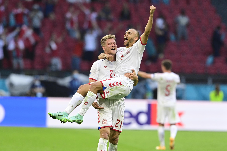 Andreas Cornelius porte en triomphe Martin Braithwaite, dernier buteur du Danemark lors du 8e de finale de l'Euro gagné contre le pays de Galles le 26 juin 2021 à Amsterdam