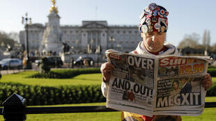 "Royal super fan John Loughery holds a copy of a British newspaper as he poses for the media outside of Buckingham Palace in London on January 9, 2020, following the announcement that Britain's Prince Harry, Duke of Sussex and his wife Meghan, Duchess of Sussex, plan to step down as ""senior"" members of the Royal Family."