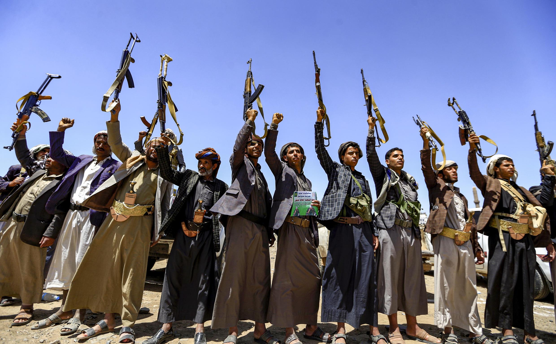 Yemeníes cantan consignas mientras sostienen rifles de asalto Kalashnikov durante una reunión tribal en la capital de los rebeldes hutiés en Saná, Yemen, en septiembre de 2019