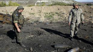 Des soldats ukrainiens constatent les dommages après un bombardement près de Lougansk, le 19 septembre 2014.