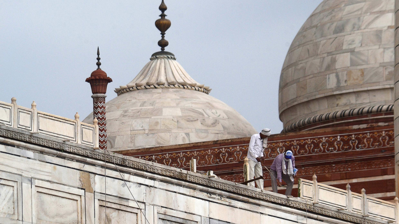 En esta imagen tomada el 30 de mayo de 2020, los trabajadores se paran en la baranda del Taj Mahal después de que fue dañado debido a la fuerte tormenta en Agra.