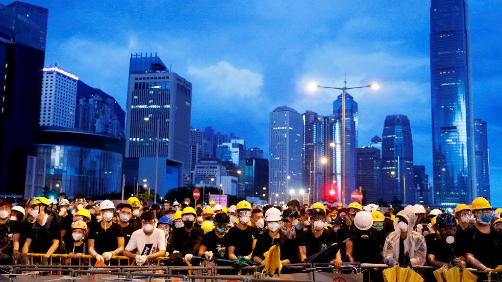 Los manifestantes antes de la ceremonia de izamiento de la bandera para el aniversario de la entrega de Hong Kong a China por parte de Reino Unido, 1 de julio de 2019.