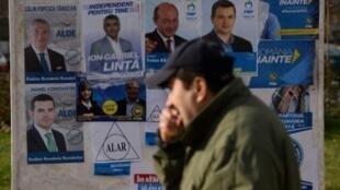مواطن روماني يمر أمام ملصقات انتخابية في بوخارست في 9 كانون الأول/ديسمبر 2016