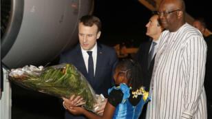 Emmanuel Macron est accueilli à l'aéroport de Ouagadougou, lundi 27 novembre 2017, par le président Roch Marc Christian Kabore.