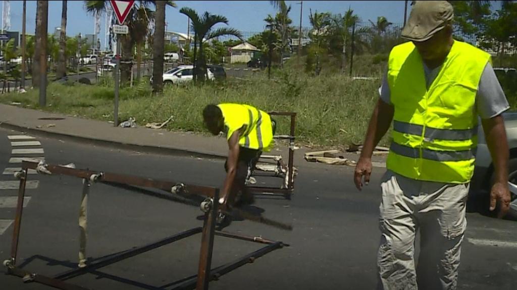 """Dos hombres participan en una manifestación de los llamados """"chalecos amarillos"""" contra aumento en el precio del combustible, en la isla La Reunión, el 21 de noviembre de 2018."""