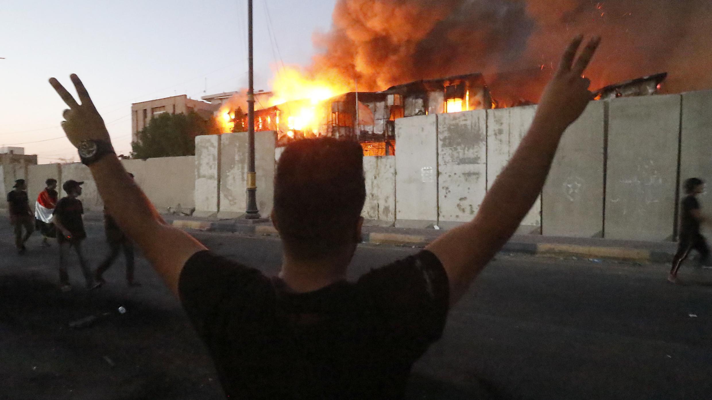 Un manifestant devant un bâtiment officiel en flammes à Bassora, le 6 septembre 2018.