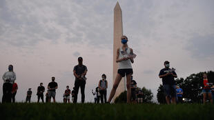 Members of  the Covid Memorial Project hold American flags in front of the Washington monument to commemorate the victims of the coronavirus