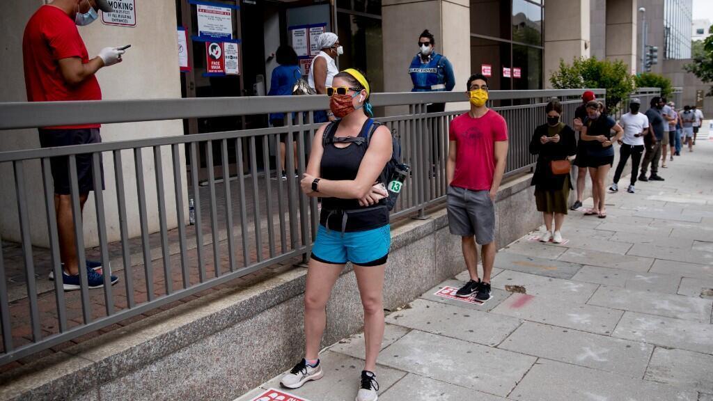 Varias personas, equipadas con máscaras, esperan en la fila para votar en un colegio electoral durante la votación de las primarias en Washington, el martes 2 de junio de 2020.