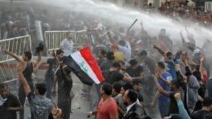 تفريق المتظاهرين باستخدام خراطيم المياه في ساحة التحرير ببغداد، 20 تموز/يوليو 2018.