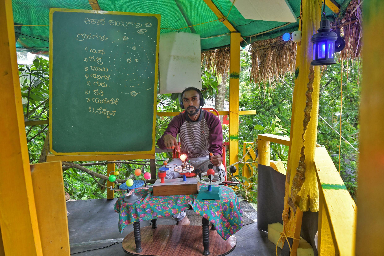 El profesor C.S. Satheesha dicta una clase  por teléfono desde una choza de su jardín, el 13 de julio de 2021 en el distrito de Kodagu (India)