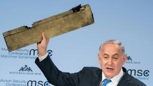 رئيس الوزراء الإسرائيلي بنيامين نتانياهو يلوح بقطعة معدنية يؤكد أنها من طائرة بدون طيار إيرانية أسقطتها إسرائيل فوق أراضيها الأسبوع الماضي، خلال مؤتمر ميونيخ للأمن في 18 شباط/فبراير 2018