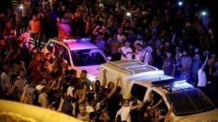 متظاهرون فلسطينيون يحاولون قطع الطريق أمام سيارات الشرطة الإسرائيلية خارج باب الأسباط المؤدي إلى باحة المسجد الأقصى في القدس القديمة في 22 تموز/يوليو 2017