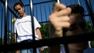 """Three teens wearing t-shirts with """"#ClassroomsNotCages"""" scrawled across the front stood inside a small cage erected outside the gates of the United Nations's European headquarters"""