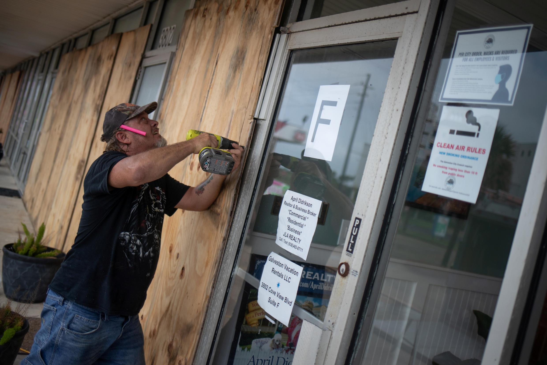 Un homme protègeant les locaux de son entreprise avant le passage de l'ouragan Laura, le 26 août 2020 à Galveston, au Texas.
