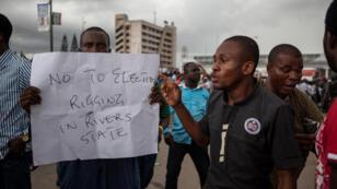 """Des partisans de l'APC ont manifesté à Port Harcourt contre l'élection en raison de """"fraude dans le Rivers state"""", comme l'indique la pancarte de cet homme."""