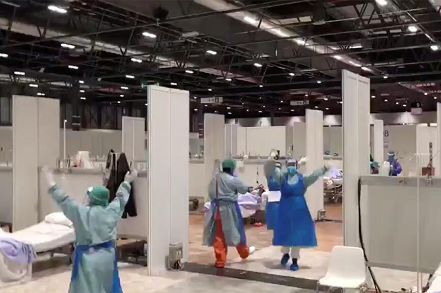 طاقم طبي يرقص على أنغام الموسيقى وسط مستشفى ميداني مملوء بمصابين بفيروس كورونا بهدف نشر الفرح والبهجة بين المرضى في مدريد، إسبانيا في 31 مارس/آذار 2020