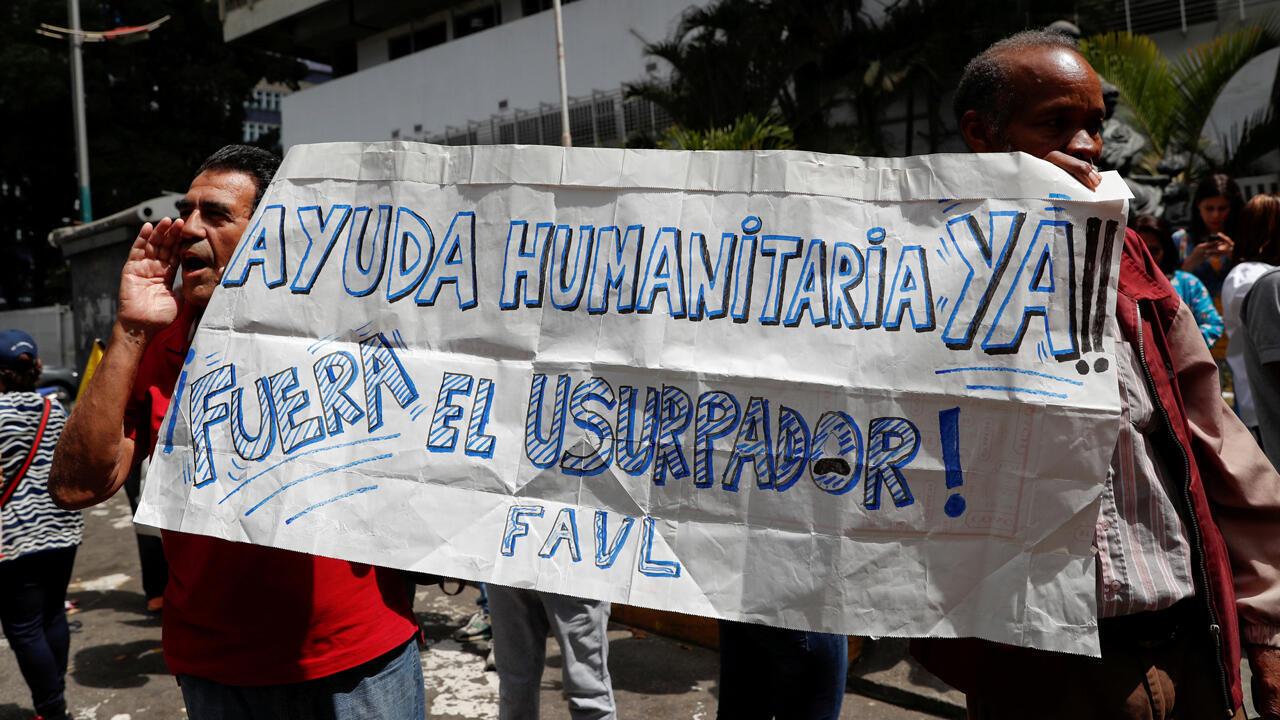 """Partidarios del  líder de la oposición y proclamado presidente interino Juan Guaidó sostienen una pancarta con la leyenda """"Ayuda humanitaria ya...fuera del usurpador"""" durante una protesta en contra del Gobierno del presidente Nicolás Maduro, en Caracas, Venezuela 30 de de enero de 2019."""