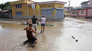 Vecinos de La Lima, cerca de San Pedro Sula (Honduras), tratan de cruzar una calle inundada por las fuertes lluvias de Iota, el 19 de noviembre de 2020