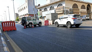 Saudi police close a street leading to a non-Muslim cemetery in the city of Jeddah where a bomb struck a World War I commemoration attended by European diplomats