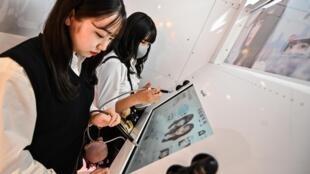 """Des adolescentes éditent leurs photos prises dans un photomaton """"purikura"""", le 21 juillet 2020 à Tokyo"""