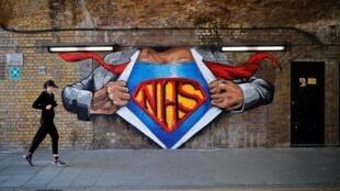 Una corredora pasa por delante de un mural dedicado a los trabajadores del Servicio Nacional de Salud británico (NHS) en el centro de Londres el 5 de mayo de 2020