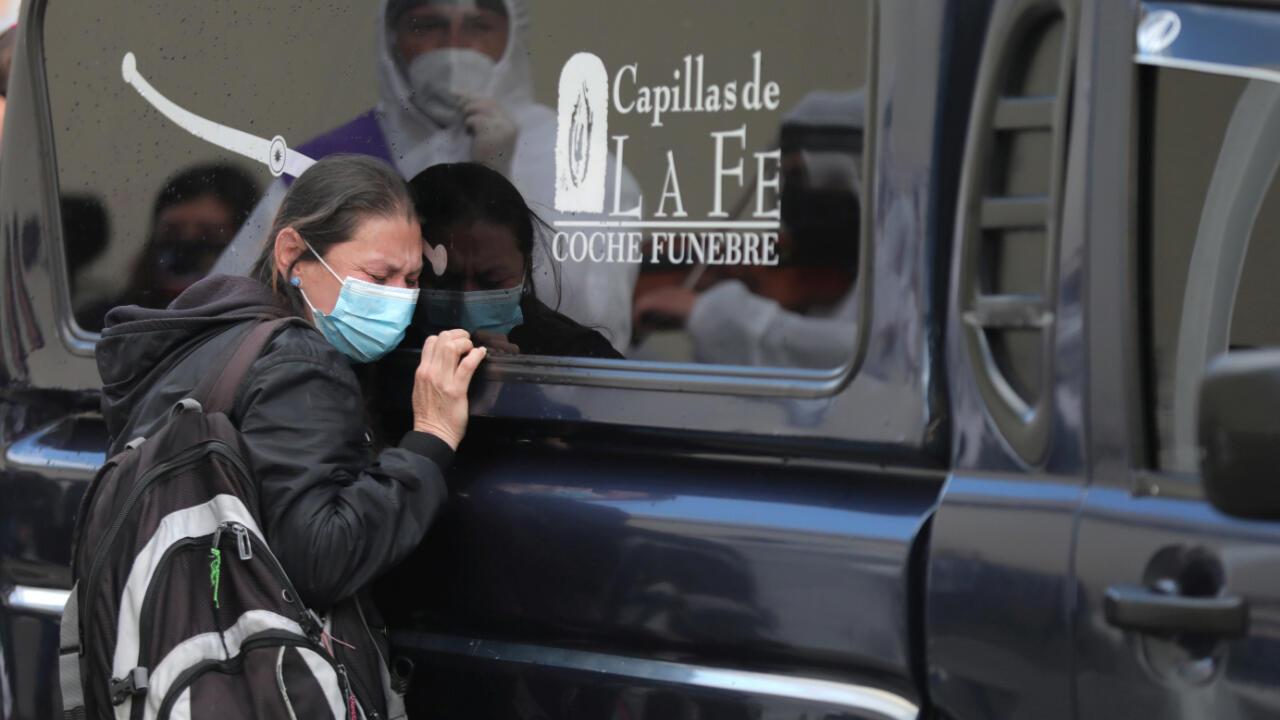 El 10 de agosto de 2020 una mujer en Bogotá, Colombia, se para al lado de un carro fúnebre para despedir a su ser querido que murió por Covid-19.
