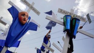 """Manifestantes sostienen cruces  durante la """"Marcha de las Flores"""" en contra el gobierno nicaragüense del presidente Daniel Ortega en Managua, el 30 de Junio de 2018."""