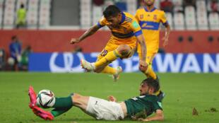 El atacante mexicano de Tigres Javier Aquino (C), intenta escapar de la marca del defensa uruguayo del Palmeiras, Matías Viña, en partido semifinal del Mundial de Clubes jugado el 7 de febrero de 2021 en Ar-Rayyan